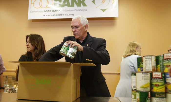 Vice President Mike Pence packs canned food into a meal box at Community Food Bank of Eastern Oklahoma during his visit to Tulsa on June 4, 2019. (Ian Maule/Tulsa World via AP)