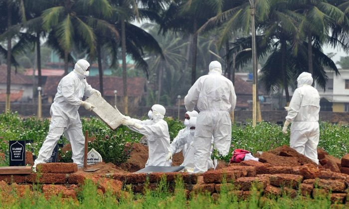 Doctors and relatives wearing protective gear dig a grave to bury the body of a Nipah virus victim on May 24, 2018.(Stringer/Reuters)