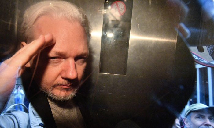 WikiLeaks founder Julian Assange gestures from the window of a prison van as he is driven out of Southwark Crown Court in London on May 1, 2019. (Daniel Leol-Olivas/AFP/Getty Images)