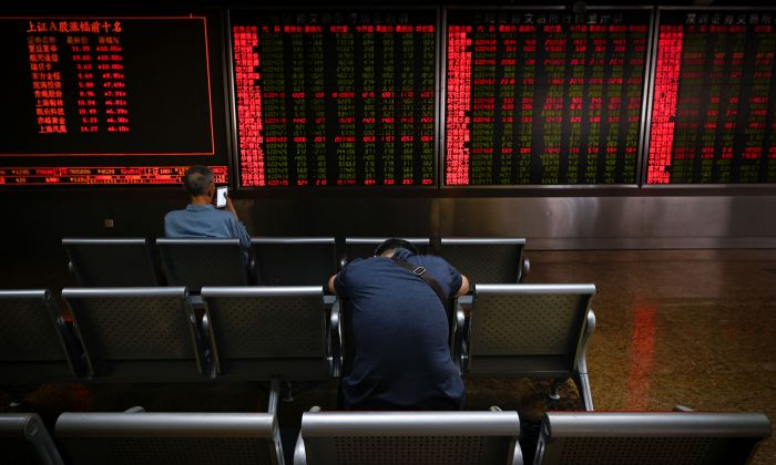 Investors rest on a chair in front of screens showing stock market movements at a securities company in Beijing on May 14, 2019. (WANG ZHAO/AFP/Getty Images)