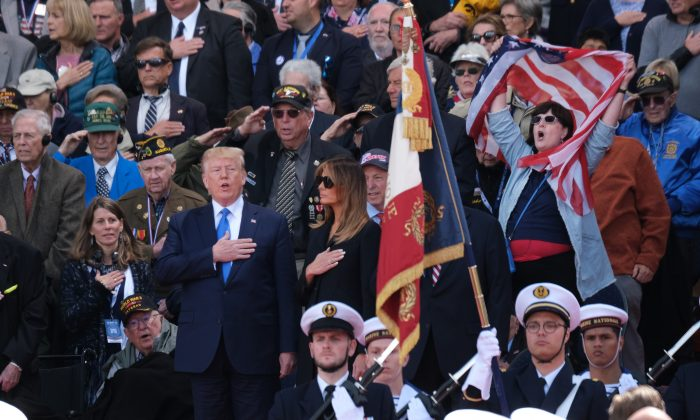 President Donald Trump sings the American national anthem as First Lady Melania Trump looks on at the main ceremony to mark the 75th anniversary of D-Day at Normandy American Cemetery, France, on June 6, 2019. (Sean Gallup/Getty Images)