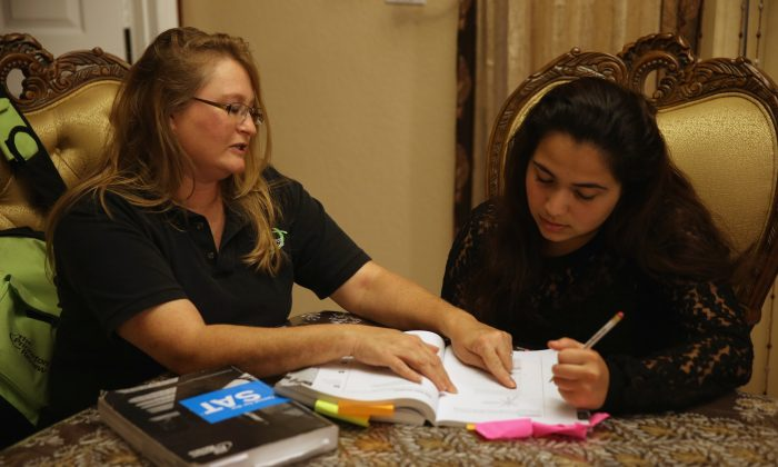Carol McMullen-Pettit, a Premier Tutor at The Princeton Review, (L) goes over SAT test preparation with 11th grader, Suzane Nazir,  on March 6, 2014 in Pembroke Pines, Florida. Joe Raedle/Getty Images