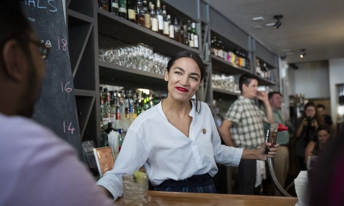 Rep. Alexandria Ocasio-Cortez works behind the bar at the Queensboro Restaurant, May 31, 2019 in the Queens borough of New York City. (Drew Angerer/Getty Images)