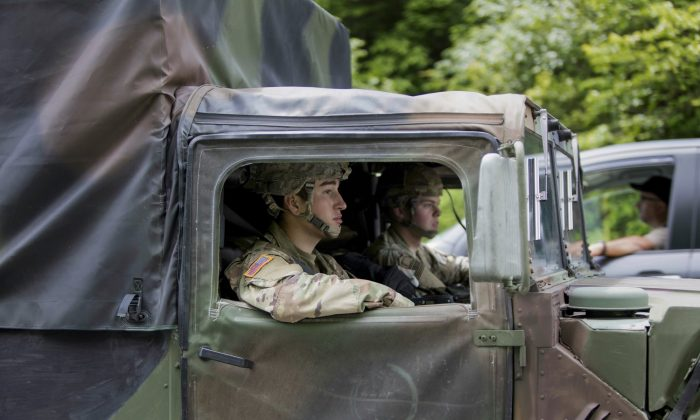 West Point cadets drive along Route 293 near the site where a light medium tactical vehicle overturned, on June 6, 2019. (Allyse Pulliam/AP Photo)