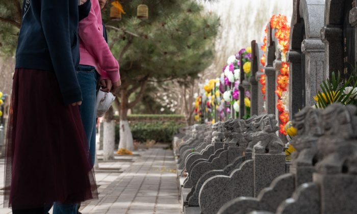 People standing in front of graves in China. (Fred Dufour/AFP/Getty Images)