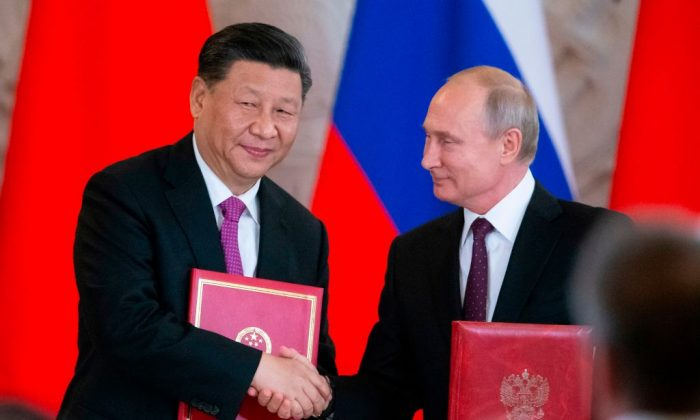 Russian President Vladimir Putin and his Chinese counterpart Xi Jinping exchange documents during a signing ceremony following their talks at the Kremlin in Moscow on June 5, 2019. (Alexander Zemlianichenko/AFP/Getty Images)