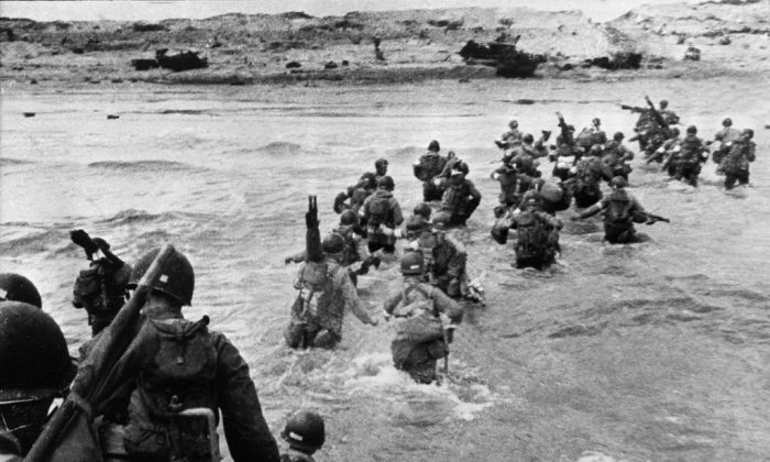 American troops landed on Normandy beaches (north-west of France), to come as reinforcements during the historic D-Day, June 6, 1944, during WW2. American troops supporting those already on the coast of Northern France, plunge into the surf and wade shoreward carrying equipment, on Utah Beach, Les Dunes de Madeleine, France. Bulldozers and other engineer equipment prepare the beach for the landing parties. (STF/AFP/Getty Images)