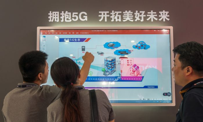 People watch a screen showing information on 5G technology during the Mobile World Conference in Shanghai on June 27, 2018. (-/AFP/Getty Images)