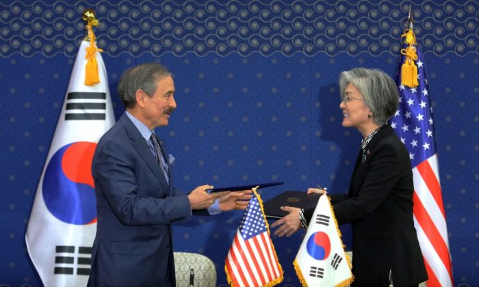 South Korea's Foreign Minister Kang Kyung-wha (R) and US Ambassador to South Korea Harry Harris exchange documents at the Foreign Ministry in Seoul on March 8, 2019. (Ahn Young-joon/AFP/Getty Images)