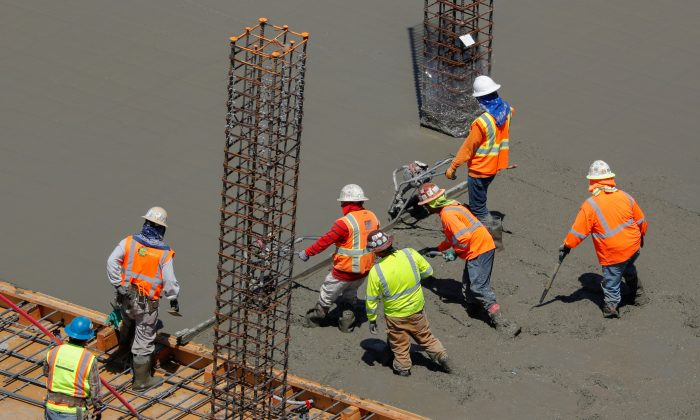 Workers pour cement at a construction site for an office town in downtown San Diego, Calif., on April 23, 2019. (Reuters/Mike Blake)