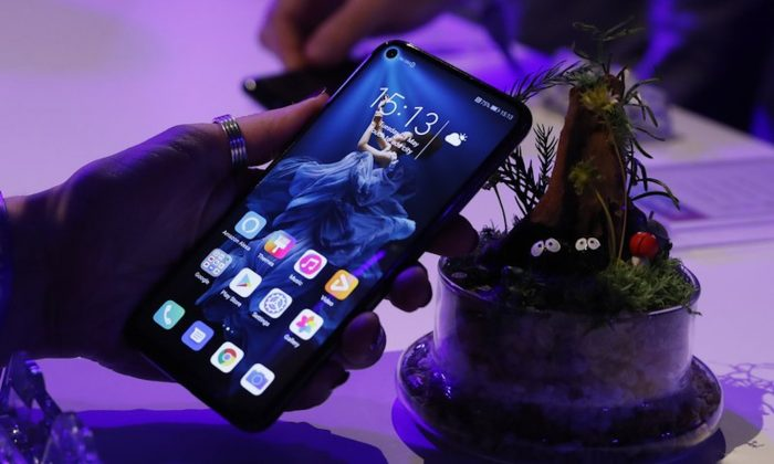 A member of the media tries out new Huawei Honor 20 series of phones following their global launch in London on May 21, 2019. Facebook said on June 7 it suspended providing software for Huawei to put on its devices while it reviews recently introduced U.S. sanctions. (Alastair Grant/AP)