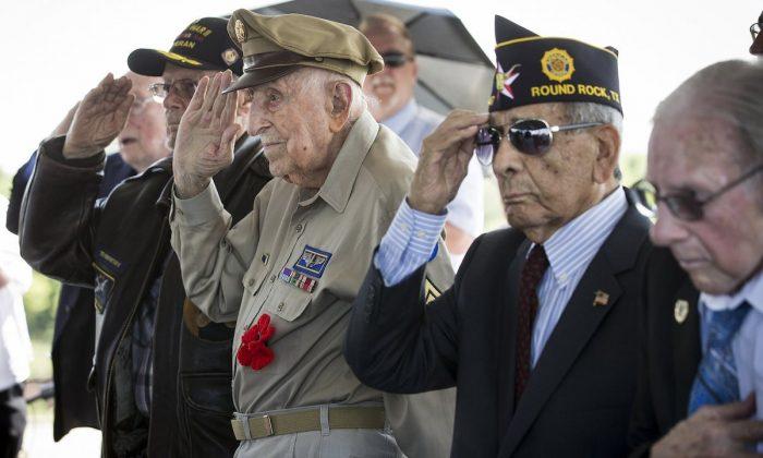 D-Day veterans, from left, Teddy Kirkpatrick, Achilles Kozakis and Robert Sanchez salute during a ceremony aboard the Battleship Texas on June 6, 2019, in La Porte, Texas. (Brett Coomer/Houston Chronicle via AP)