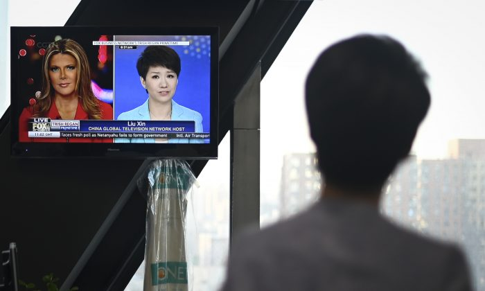China's state broadcaster CGTN anchor Liu Xin looks at a screen showing her debate with Fox Business Network presenter Trish Regan, at the CCTV headquarters in Beijing on May 30, 2019. (Wang Zhao/AFP/Getty Images)