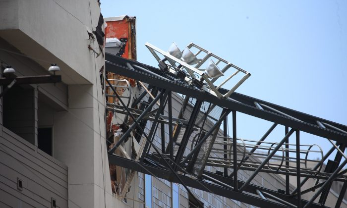 Officials respond to the scene after a crane collapsed into Elan City Lights apartments amid severe thunderstorms in Dallas, Texas on June 9, 2019. (Shaban Athuman/The Dallas Morning News via AP)