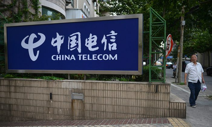A pedestrian walks past a China Telecom sign on a street in Shanghai on August 21, 2013. (PETER PARKS/AFP/Getty Images)
