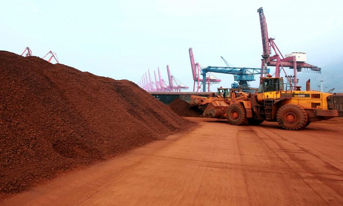 A man driving a front loader shifts soil containing rare earth minerals to be loaded at a port in Lianyungang, east China's Jiangsu province, on Sept. 5, 2010. (STR/AFP/Getty Images)