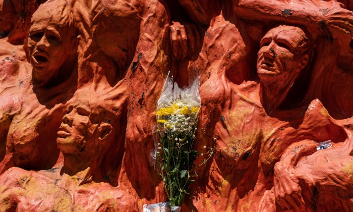 Flowers are placed in front of the 'Pillar of Shame' statue, an art piece dedicated to the victims of the 1989 Beijing Tiananmen Square massacre, at the University of Hong Kong in Hong Kong, China, on June 4, 2019. (Anthony Kwan/Getty Images)
