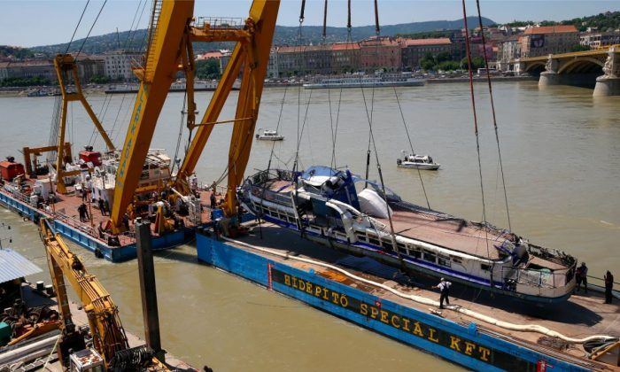 A crane lifts the sightseeing boat out of the Danube river in Budapest, Hungary, on June 11, 2019. (AP Photo/Darko Bandic)