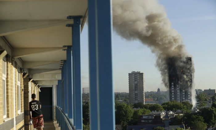 A resident in a nearby building watches smoke rise from a building on fire in London on June 14, 2017. (Matt Dunham, File photo via AP)