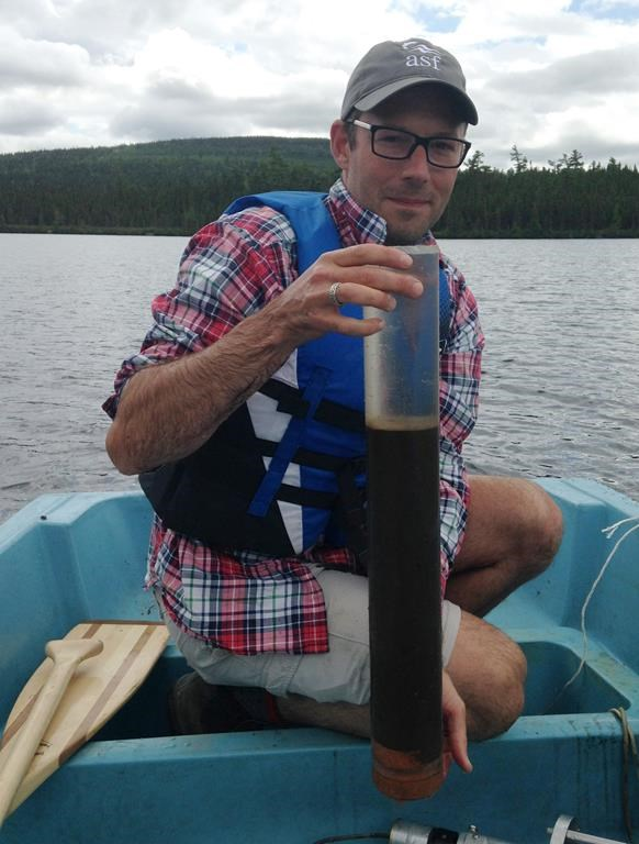 Environmental scientist and lead author Dr. Josh Kurek with a lake sediment core from Sinclair Lake, New Brunswick is shown in this handout image. (HO-Dr.Josh Kurek/The Canadian Press)