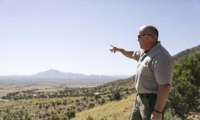 Cochise County Sheriff Mark Dannels points to the U.S.–Mexico border in Sierra Vista, Arizona, on May 5, 2019. (Charlotte Cuthbertson/The Epoch Times)