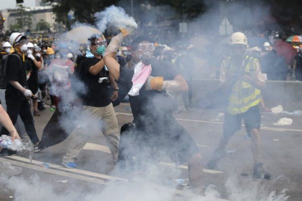 A demonstrator throws a canister of tear gas back towards the police outside the Legislative Council
