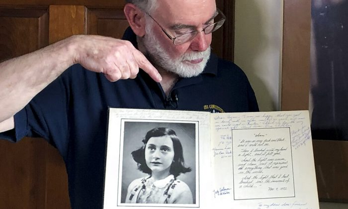 In this June 7, 2019 photo, Ryan Cooper holds a 1972 portion of a diary that he wrote when he visited Otto Frank, the father of the famed Holocaust victim and diarist Anne Frank, at his home in Yarmouth, Mass. The diary includes a photo of Anne Frank and the autographs of other people he met who knew her. Cooper has donated a trove of letters and mementos he received from Otto Frank to the U.S. Holocaust Memorial Museum ahead of the 90th anniversary of Anne Frank's birthday. (Philip Marcelo/AP Photo)