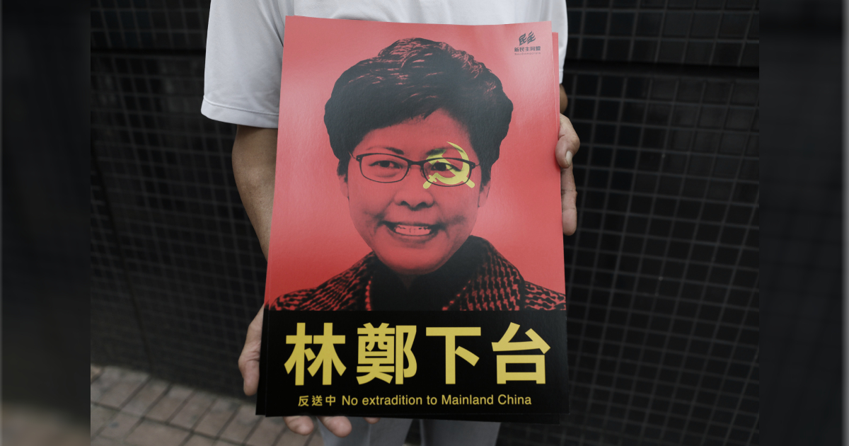 A protester holds posters showing Hong Kong Chief Executive Carrie Lam