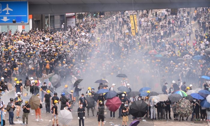 Police fired tear gas toward the protesters over 10 times near the Legislative Council of Hong Kong on June 12, 2019. (Song Bilong/The Epoch Times)