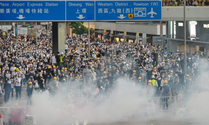 Protestors are shrouded in tear gas during a protest against proposed extradition bill near Hong Kong's Legislative Council on June 12, 2019. (Song Bilong/The Epoch Times)