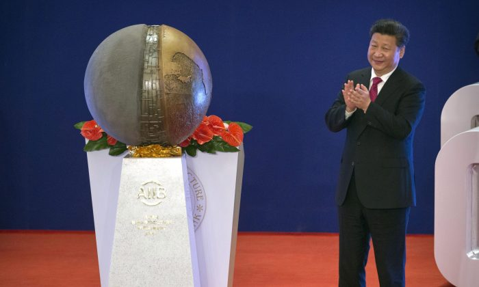 Chinese leader Xi Jinping applauds after unveiling a sculpture during the opening ceremony of the Asian Infrastructure Investment Bank (AIIB) in Beijing on Jan. 16, 2016. (AP Photo/Mark Schiefelbein, Pool)