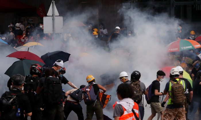 Protesters react to a tear gas during a demonstration against a proposed extradition bill in Hong Kong, on June 12, 2019. (Athit Perawongmetha/Reuters)
