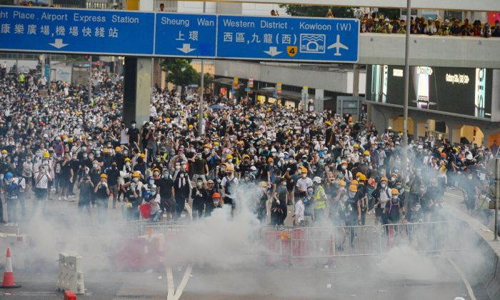 As mass protests intensified, Hong Kong police fired tear gas and rubber bullets at of protesters on June 12, 2019 outside Hong Kong's Legislative Council building. (Bilong Song/The Epoch Times)