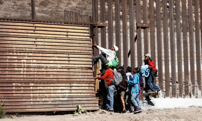 Migrants break through the old U.S. border fence just beyond the east pedestrian entrance of the San Ysidro crossing in Tijuana, Mexico, on Nov. 25, 2018. (Charlotte Cuthbertson/The Epoch Times)