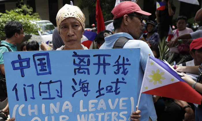 A protester holds a slogan during a rally outside the Chinese Consulate in the financial district of Makati, metropolitan Manila, Philippines to mark Independence Day on June 12, 2019. The Philippine defense secretary says an anchored Filipino fishing boat has sunk in the disputed South China Sea after being hit by a suspected Chinese vessel which then abandoned the 22 Filipino crewmen. (Aaron Favila/AP)