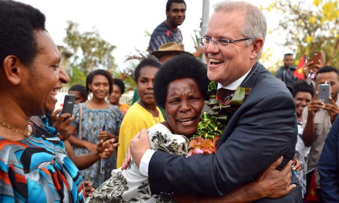 Australia's Prime Minister Scott Morrison is hugged by a woman as he greets locals at the opening of a new building at the University of Papua New Guinea after an Asia-Pacific Economic Cooperation forum in Port Moresby, Papua New Guinea on Nov. 18, 2018.   (Mick Tsikas/Pool via Reuters)