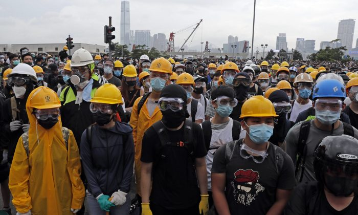 Protestors wear masks and helmets to protect their identities near the Legislative Council in Hong Kong on June 12, 2019. Young Hong Kong residents protesting a proposed extradition law that would allow suspects to be sent to China for trial are seeking to safeguard their identities from potential retaliation by authorities employing mass data collection and sophisticated facial recognition technology. (Kin Cheung/AP)