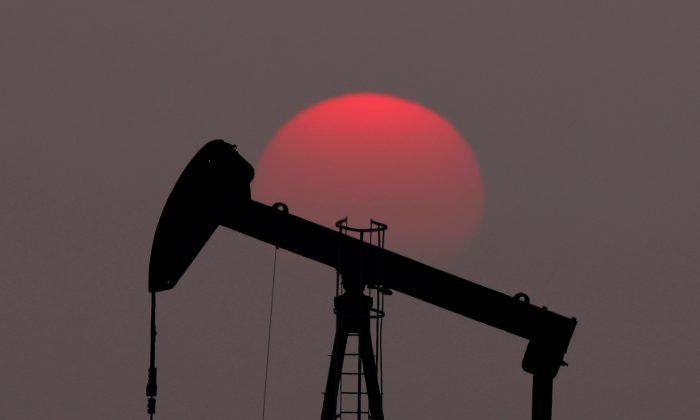 The sun sets behind an oil pump outside Saint-Fiacre, near Paris, France on March 28, 2019. (Christian Hartmann/Reuters)