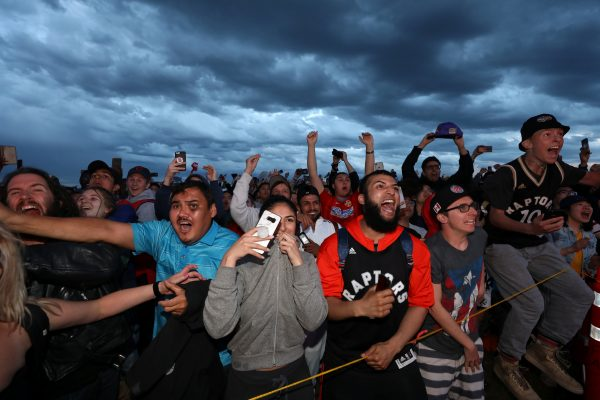 Fans react as the Toronto Raptors defeat the Golden State Warriors in the NBA Finals while watching on a large screen in a fan zone in Calgary, Alberta, Canada, June 13, 2019. (Todd Korol/Reuters)