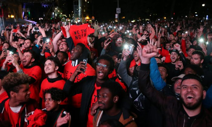 Fans celebrate their win in Game 6 of the NBA basketball Finals between the Toronto Raptors and the Golden State Warriors on a large screen in a fan zone in Montreal, Quebec, Canada, June 13, 2019.  (Christinne Muschi/Reuters)