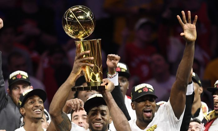 Toronto Raptors forward Kawhi Leonard, centre, holds Larry O'Brien NBA Championship Trophy after defeating the Golden State Warriors basketball action in Game 6 of the NBA Finals in Oakland, Calif. on Thursday, June 13, 2019. Raptors have won their first NBA title in franchise history. (Frank Gunn/The Canadian Press)