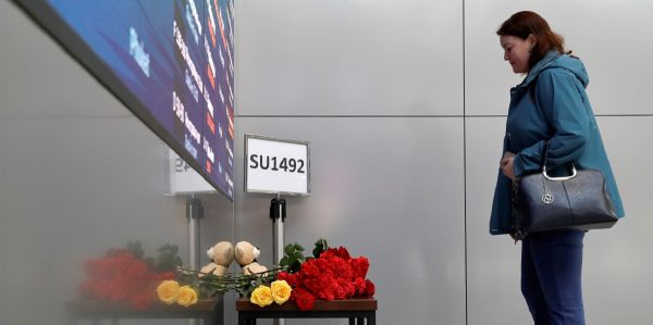A woman commemorates victims of an incident involving an Aeroflot Sukhoi Superjet 100 passenger plane