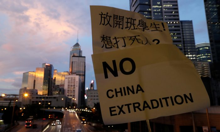 A placard is displayed during a protest following a day of violence over a proposed extradition bill, near the Legislative Council building in Hong Kong, China on June 13, 2019. (Jorge Silva/Reuters)