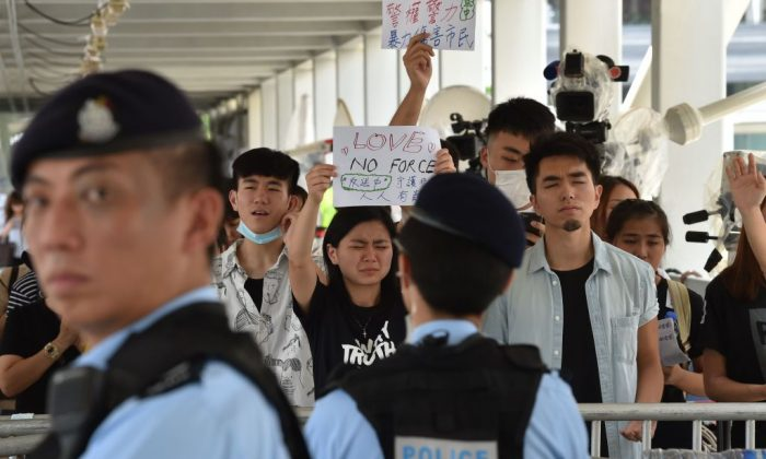 Police stand guard as protesters display placards during a demonstration against a proposed  extradition bill near the government headquarters in Hong Kong on June 14, 2019. (Hector Retamal/AFP/Getty Images)