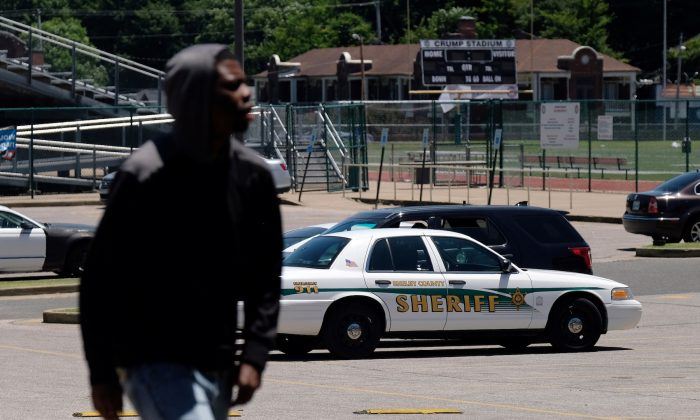 A young man walks in front of a police patrol parked in front of a high school a day after violent clashes between police and protesters broke out on streets overnight in Memphis, Tenn., on June 13, 2019. (Ricardo Arduengo/Reuters)
