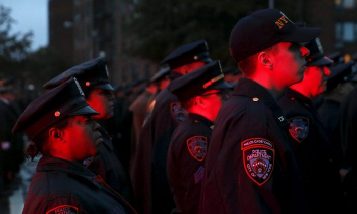 Police are lit by flashing lights as they stand in formation while the casket of slain New York City Police officer Randolph Holder is carried from the Greater Allen A.M.E. Cathedral of New York following his funeral service in the Queens borough of N.Y.C., on Oct. 28, 2015. (Shannon Stapleton/Reuters/File Photo)