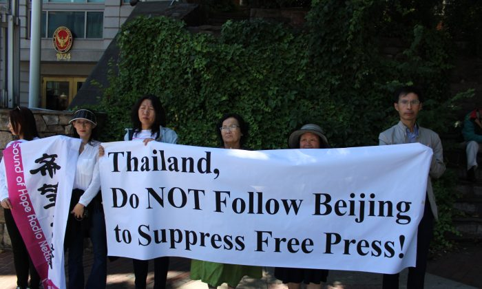 Protesters hold a sign opposite the Thai Embassy in Washington on June 14, 2019. (Joan Chang/The Epoch Times)