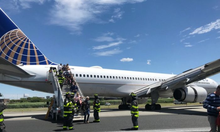 Emergency personnel help passengers off a plane after a United Airlines plane skidded off the runway after landing at Newark Liberty International Airport in Newark, N.J., on June 15, 2019. (Caroline Craddock via AP)