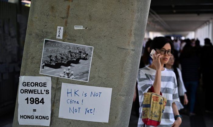 People walk past placards against a controversial extradition law proposal pasted on a wall near the Legislative Council Complex in Hong Kong on June 14, 2019. (Hector Retamal/AFP/Getty Images)
