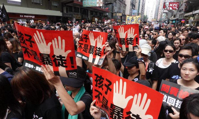 "Protesters hold up Chinese signs that read ""Children Are Not Rioters"" in a march in Hong Kong on June 16, 2019. (Yu Gang/The Epoch Times)"
